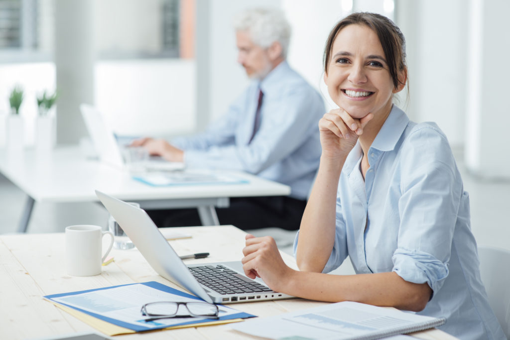 Smiling young business woman sitting at office desk and working with a laptop, she is looking at camera