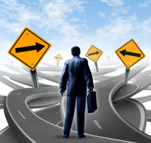 Strategic journey as a business man with a breifcase choosing the right strategic path for a new career with blank yellow traffic signs with arrows tangled roads and highways in a confused direction.